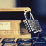 Credit card with padlock on laptop for PCI Secure Software Standard